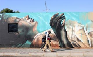 A couple walk past an art work by German artist @norm_abartig and South African artist @dekor as part of the Westdene Graffiti Project in downtown Johannesburg, South Africa, 09 October 2018.