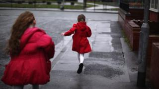 Two children run in the street