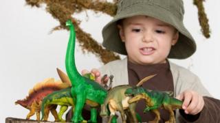 Niño jugando con dinosaurios.