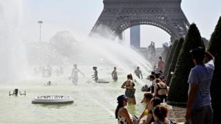 Gente bañándose en las fuentes frente a la Torre Eiffel.