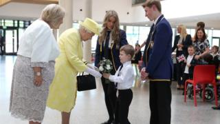 Queen Elizabeth receives a posy of flowers from Archie Wilson alongside Elise McCormick and Cameron MacIndoe watched by headteacher Linda Park during a visit to Greenfaulds High School in the west of Cumbernauld