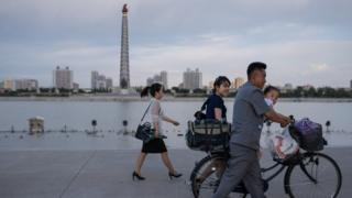 Pyongyangites go about their daily business with the Tower of Juche in the background