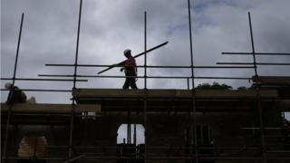A builder assembles scaffolding as he works on new homes