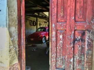 Volkswagen Beetle seen through a door that's ajar