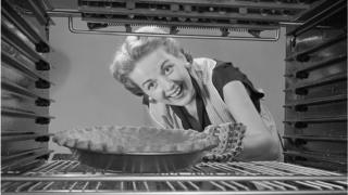 Woman looking at pie in oven