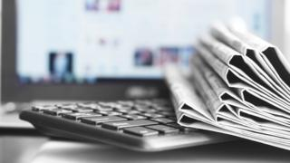 A stack of folded newspapers sits on a keyboard in front of a monitor showing a blurred news website