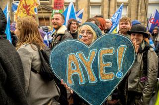 """Woman with banner saying """"aye"""""""