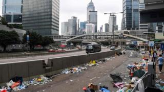 People walk on a street full of debris a day after a demonstration against a controversial extradition law proposal in Hong Kong