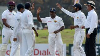 "A file picture taken on October 16, 2015 shows Sri Lankan spinner Rangana Herath (C) being congratulated by teammates at the close of play of the West Indies"" first innings during the third day of the opening"