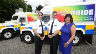 Police officer stand with 'Pride' Land Rovers