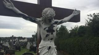 A damaged statue of Christ on a crucifix