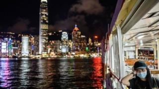 A woman wearing a face mask takes a Star Ferry in Victoria Harbour from Kowloon side to Hong Kong Island (back) on July 27, 2020