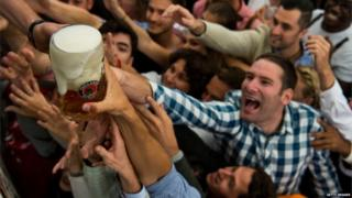 Visitors reach for one-litre glasses of free beer to kick off the 2016 Oktoberfest beer festival