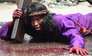 A man lies on the ground carrying a crucifix during a dramatisation of the crucifixion of Jesus Christ to mark Good Friday, heralding the start of Easter celebrations, in Lagos on March 30, 2018.