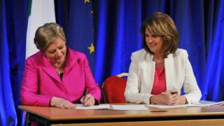 Irish Minister for Justice Frances Fitzgerald (L) signs the commencement order for the Marriage Act 2015 in front of Deputy Prime Minister (Tanaiste) Joan Burton
