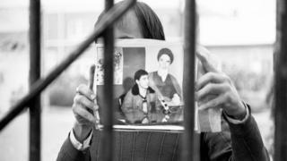 Eyleme katılan öğrencilerden biri, rehin tuttuğu kişinin fotoğrafını gösteriyor