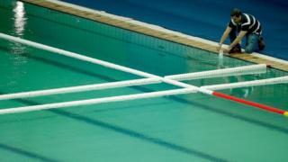 Técnico retira amostra da piscina do Centro Aquático, cuja água esverdeou