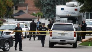 Police stand at a crime scene in front of a house where three people have died in an incident involving a crossbow.