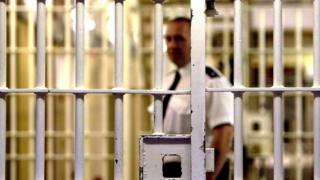 UK prison guard standing behind some prison bars