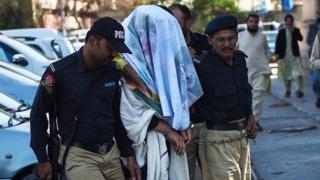 پاکستاني پولیسو د پښتون ژغورنې غورځنګ نیول شوی غړی عالمزیب محسود محکمې ته بیايي، چې مخ یې پټ کړی دی.