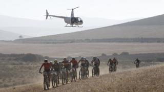 Professional riders taking part in The professional peleton race cycle on a track in Greyton, South Africa, while a helicopter hovers overheads.