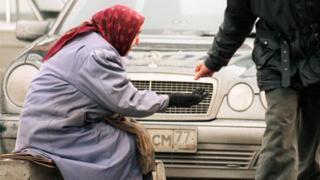 Пожилая женщина просит милостыню, сидя возле автомобиля Mercedes-Benz. Москва, 25 декабря.