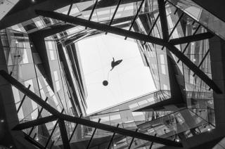 A black and white image of glass and walls in a building