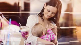 Woman breastfeeding outside cafe
