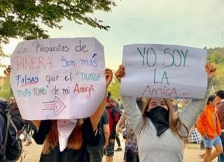 Dos mujeres sostienen carteles