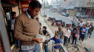 A man counts Indian rupee banknotes after withdrawing them from an ATM in Agartala, India,