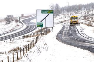 A snow plough works on a snow-covered road