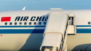 A man wearing personal protective equipment (PPE) looks outside the Air China aeroplane which arrived with a team health experts from China, that will help with the fight against the COVID-19 coronavirus, and medical equipment at the Robert Mugabe International Airport in Harare on May 11, 2020.