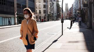 A masked woman walks the deserted streets of London