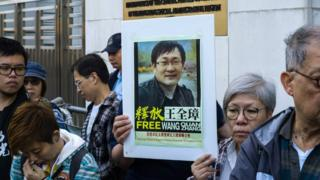 Activists hold a placard of detained Chinese human rights lawyer Wang Quanzhang at a rally outside Chinese Liaison Office in Hong Kong on December 26, 2018