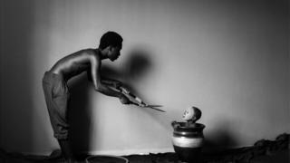 صورة من سلسلة تحمل اسم لجوء للمصور إيريك غيامفي من غانا تظهر رجلا يحمل مقص الزرع ويقترب من طفل في وعاء