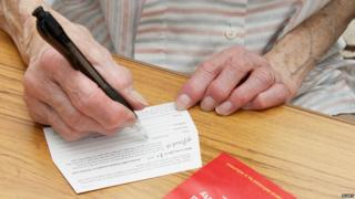 Elderly person writing on a giftaid envelope