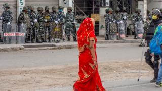Fila de agentes de la policía y una mujer india vestida de rojo