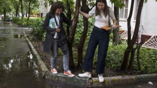 Кандидатки пробираются мимо луж во дворах