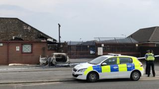 A burned out police car , two police officers and police cordon