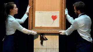 Banksy mengatur penghancur kertas untuk menghancurkan Girl with Balloon setelah dijual di rumah lelang Sotheby di London, menciptakan karya seni baru Love in the Bin