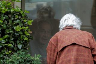 in_pictures An elderly man and woman talk to each through a closed window