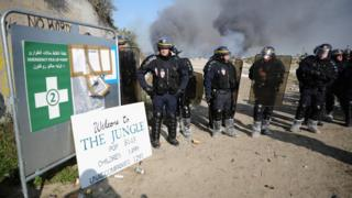 French police stand at the entrance of the migrant camp in Calais during the demolition.