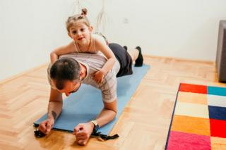 A child lies on her father's back while he does a plank exercise