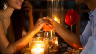 Couple holding hands at candlelit table
