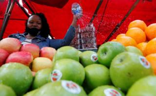 A trader waters fruits at her grocery stall amid the coronavirus disease (COVID-19) spread, in Eastleigh district of Nairobi, Kenya June 17, 2020.