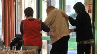 Carers helping an elderly man