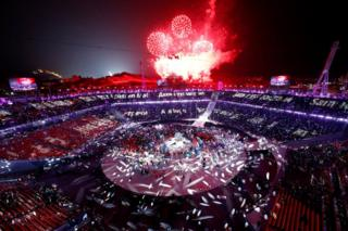Red fireworks explore over a crowded Olympic stadium