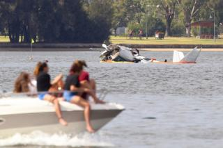 Passengers on a boat look at the debris of a plane in the Swan River in Perth, Western Australia