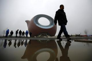 Workers stand next to a building shaped like a clay teapot in Wuxi