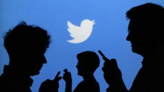 People holding mobile phones are silhouetted against a backdrop projected with the Twitter logo in this illustration picture taken in Warsaw September 27, 2013.